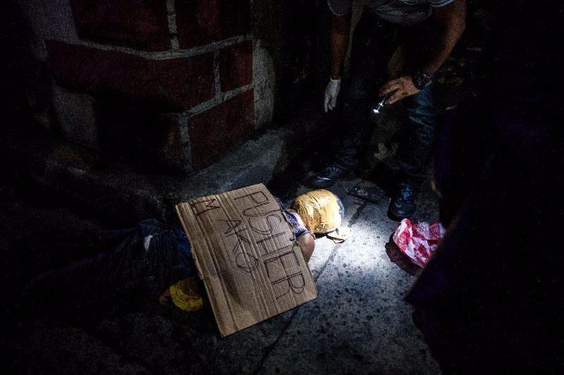 Cảnh sát điều tra hiện trường một nghi can ma túy bị những kẻ ám sát bí mật giết chết ở Manila.