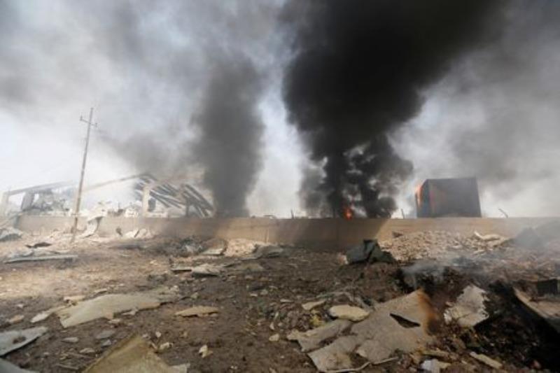 Khói bốc lên từ một khu dân cư ở Baghdad (Iraq) vì bị pháo từ kho vũ khí phát nổ bay trúng.