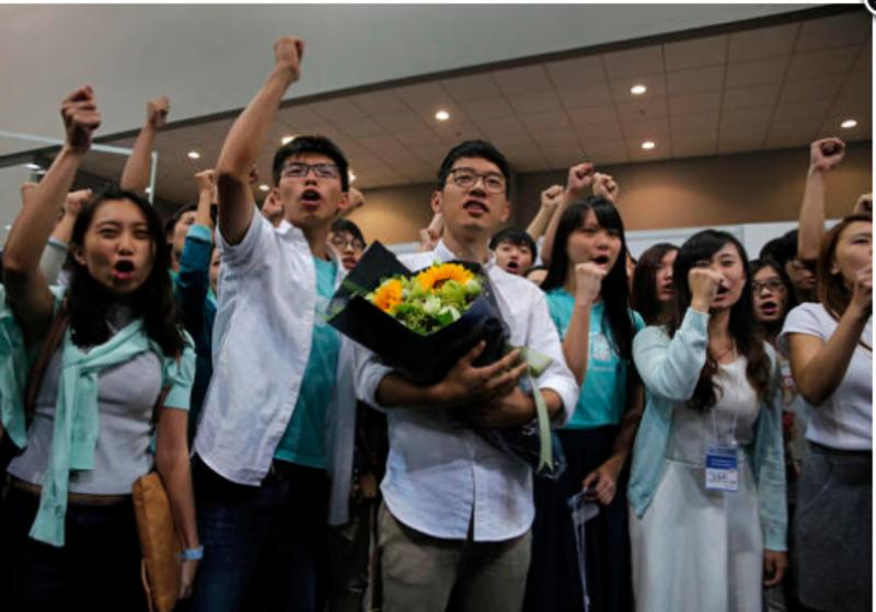 Nathan Law (cầm hoa) và lãnh đạo sinh viên Joshua Wong thuộc đảng Demosistō mừng chiến thắng ngày 5-9.