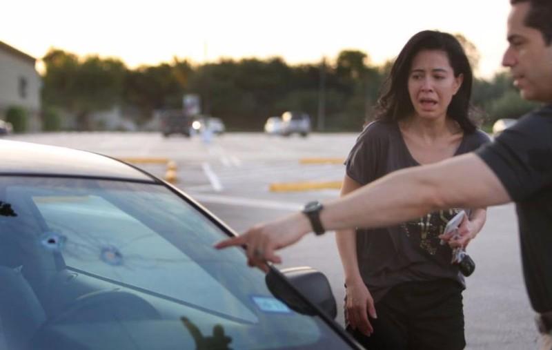 Người chồng đang chỉ cho vợ mình những vết đạn thủ phạm bắn vào xe mình trong vụ xả súng.