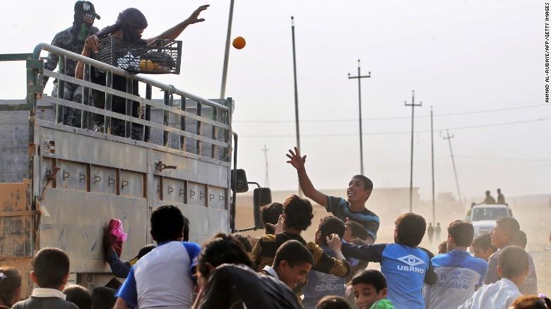 Quân Iraq phát trái cây cho người dân làng al-Khuwayn, ngoại ô phía nam Mosul sau khi chiếm lại làng này từ IS ngày 23-10.