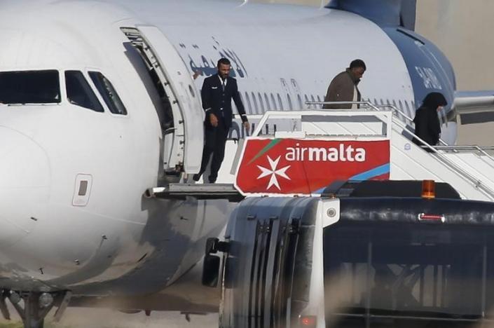 Hành khách được thả khỏi máy bay. Ảnh: REUTERS