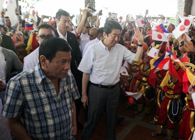 Tổng thống Duterte (trái) và Thủ tướng Abe gặp gỡ các vũ công dân gian trong một sự kiện tại Davao (Philippines) ngày 13-1. Ảnh: REUTERS