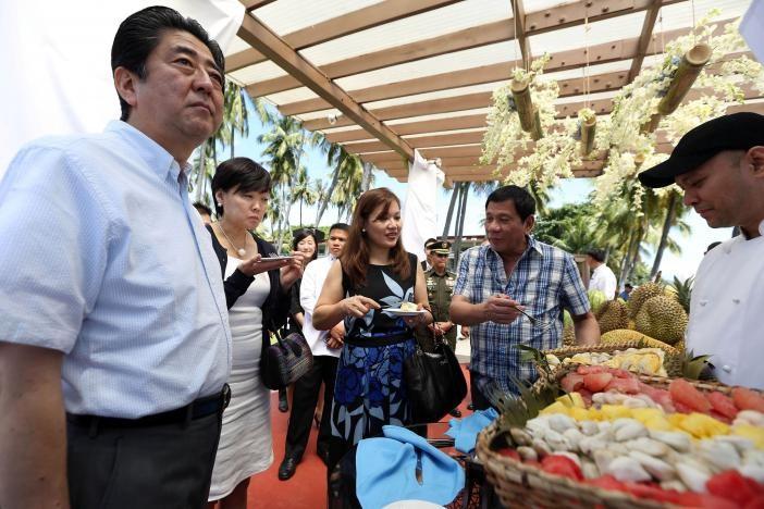 Vợ chồng Tổng thống Duterte (phải) và vợ chồng Thủ tướng Abe (trái) ăn sầu riêng trong một sự kiện tại Davao (Philippines) ngày 13-1. Ảnh: REUTERS