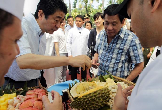 Tổng thống Duterte và Thủ tướng Abe (trái) ăn sầu riêng trong một sự kiện tại Davao (Philippines) ngày 13-1. Ảnh: REUTERS