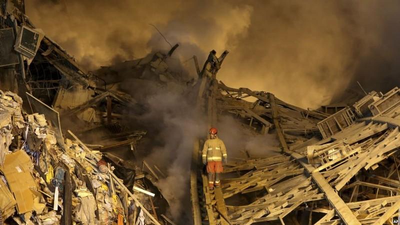 Lính cứu hỏa cố tìm đồng nghiệp trong đống đổ nát. Ảnh: AP