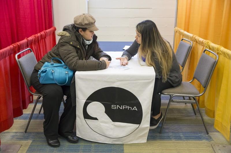Edna Cusi (trái) được Catherine Nguyễn, một sinh viên dược năm ba tại ĐH Washington, giải thích và tư vấn về kết quả đo cholesterol. Ảnh: SEATTLE TIMES