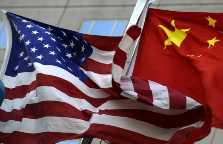 Cờ Mỹ (trái) và cờ Trung Quốc trước một khách sạn quốc tế ở Bắc Kinh (Trung Quốc). Ảnh: REUTERS