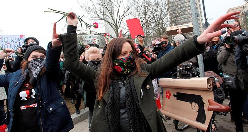 Phụ nữ ném bỏ hoa trong cuộc tuần hành trước tòa nhà Quốc hội ở Warsaw (Ba Lan) ngày 8-3. Ảnh: REUTERS