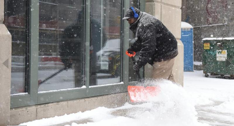 Dọn tuyết bên ngoài một cửa hàng ở Detroit (Michigan, Mỹ) ngày 13-3. Ảnh: AP