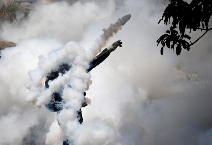 Người biểu tình ném lựu đạn cay về phía cảnh sát tại thủ đô Caracas (Venezuela) ngày 19-4. Ảnh: REUTERS