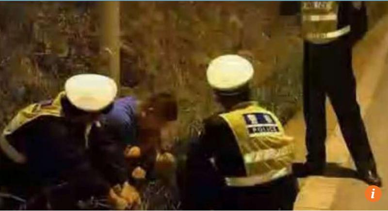 Tài xế say xỉn ngồi bứt cỏ ăn bên vệ đường. Ảnh SCMP chụp từ video