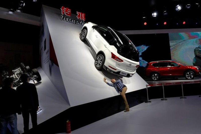 Một phụ nữ chụp hình với mẫu ô tô Trumpchi GS4 của GAC Group trưng bày tại Triển lãm ô tô Thượng Hải, Trung Quốc ngày 20-4. Ảnh: REUTERS