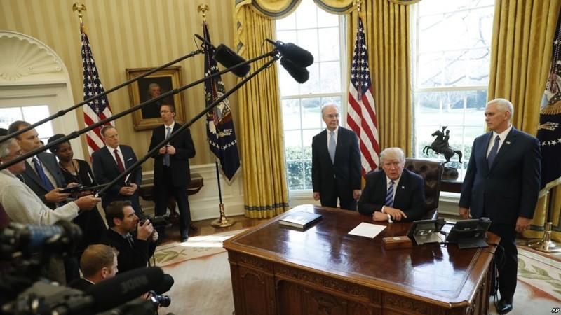Ông Trump (ngồi) họp báo tại Nhà Trắng ngày 24-3 sau khi dự luật thay thế Obamacare của ông bị Hạ viện hủy bỏ phiếu. Ảnh: AP