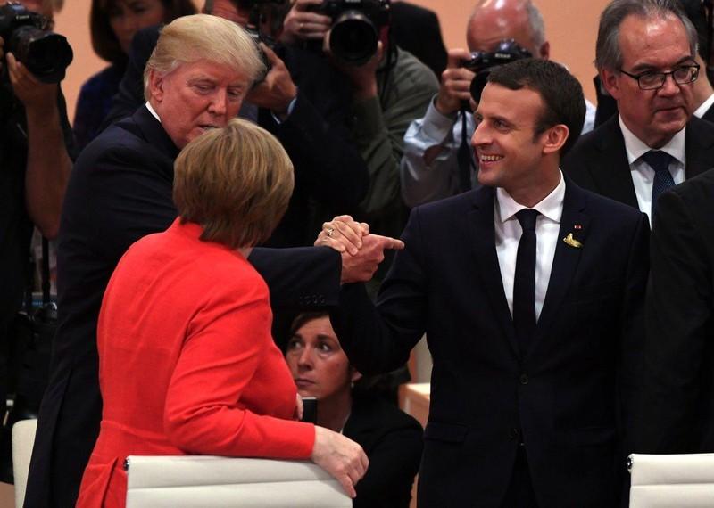 Tổng thống Mỹ Trump (trái) bắt đầu khóa tay Tổng thống Pháp Macron tại G20 trong khi vẫn nói chuyện với Thủ tướng Đức Merkel. Ảnh: NYT