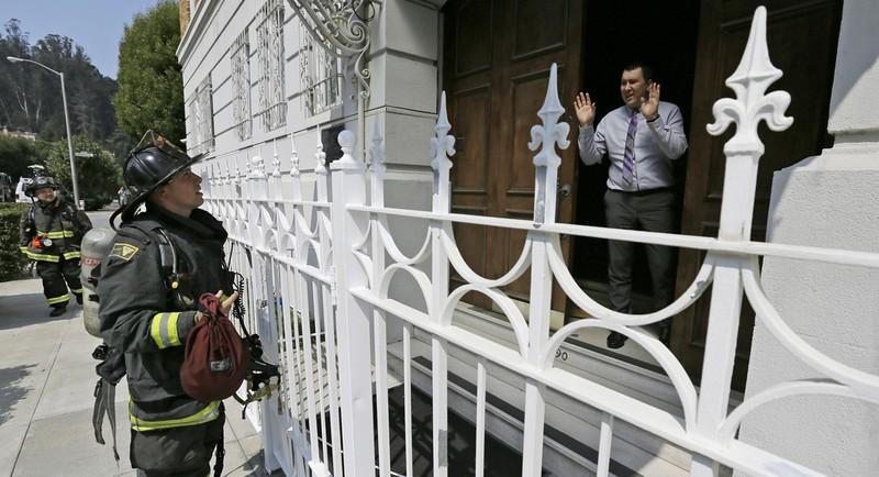 Một nhân viên lãnh sự Nga nói với lính cứu hỏa rằng không có vấn đề gì nghiêm trọng khi có khói bốc lên mái tòa tổng lãnh sự Nga ở San Francisco (Mỹ) ngày 1-9. Ảnh: AP