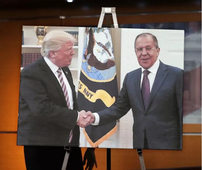 Phe Dân chủ trưng hình ảnh Tổng thống Mỹ Trump chào mừng Ngoại trưởng Nga Sergei Lavrov trong một cuộc họp báo tại Nhà Trắng. Cuộc gặp diễn ra chỉ một ngày sau khi ông Trump sa thải Giám đốc FBI James Comey. Ảnh: GETTY IMAGES