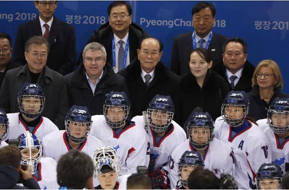 Từ trái sang): Tổng thống Hàn Quốc Moon Jae-in, Chủ tịch Ủy ban Olympic Quốc tế Thomas Bach, ông Kim Yong-nam, bà Kim Yo-jong chụp ảnh cùng đội VĐV liên Triều tại trung tâm khúc côn cầu Kwandong ở TP Gangneung, tỉnh Gangwon. Ảnh: REUTERS