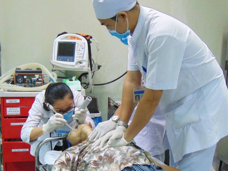 Bác sĩ và điều dưỡng đang cấp cứu bệnh nhân. Ảnh: TRẦN NGỌC