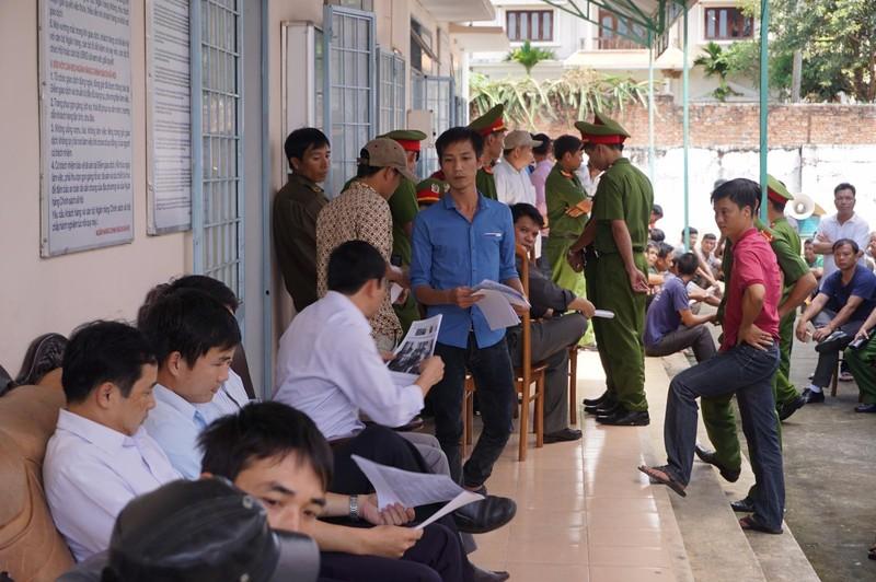 Cán bộ tòa án (áo xanh) đi gom lại bài báo của báo Pháp Luật TP.HCM để trình cho chủ tọa. Ảnh: NGÂN NGA