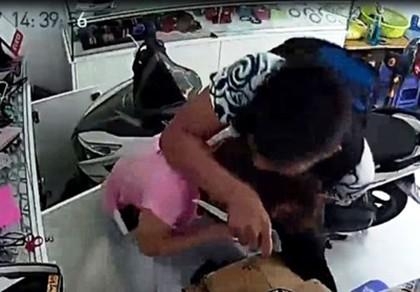 Tên cướp dí dao khống chế nhưng bị cô gái chống trả quyết liệt. Ảnh cắt từ camera.