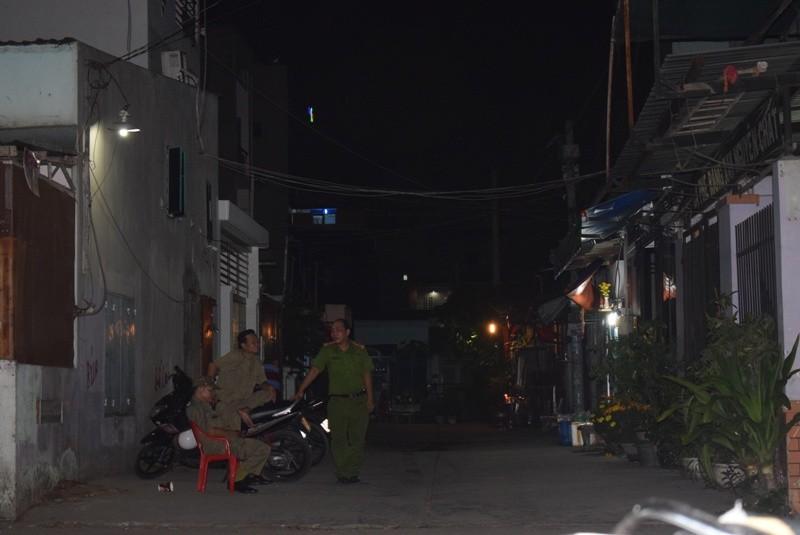 Đến tối ngày 16-2 vẫn có lực lượng công an và bảo vệ dân phố túc trực trước con hẻm vào nhà gia đình 5 người bị sát hại. Ảnh