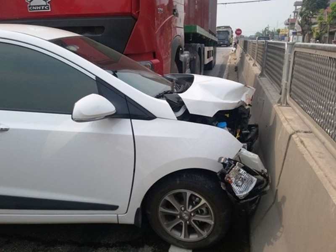 Đầu xe ôtô bị hư hỏng sau khi cạt vào giải phân cách giữa đường.