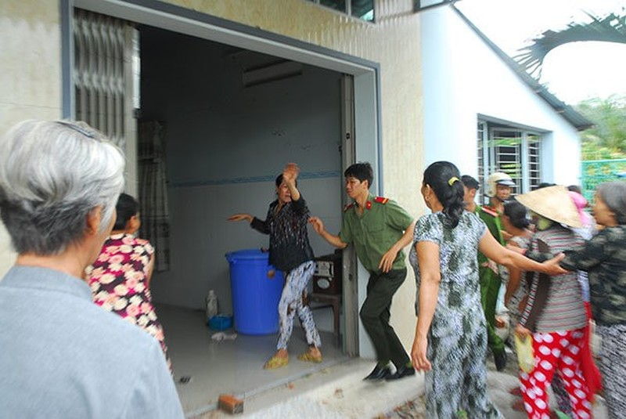 Lực lượng chức năng túc trực để ngăn cản người chơi hụi xông vào nhà bà Tư đòi nợ. Ảnh: Hoài Thương.