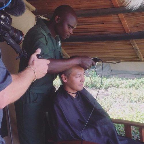 Các nhân viên trong chiến dịch bảo vệ động vật hoang dã tại Châu Phi giúp Phan Anh xuống tóc - Ảnh: NVCC