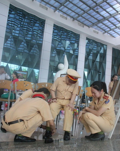 Các đoàn viên, Hội phụ nữ phòng PC67 mang giày cảnh sát cho Dũng - Ảnh: Đoàn Cường