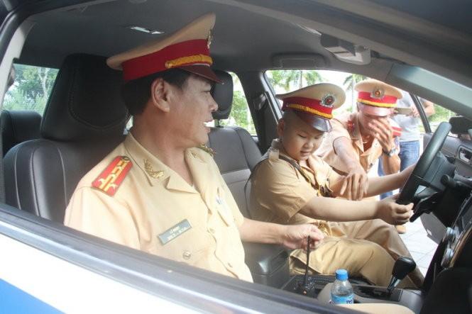 Dũng còn được đặc cách cho ngồi thử trên xe ô tô dẫn đoàn của PC67 công an Đà Nẵng - Ảnh: Đoàn Cường