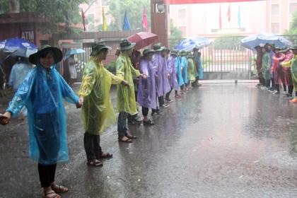 Tình nguyện viên đội mưa che chắn cho sĩ tử - ảnh 13
