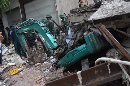 Một chiếc xe cẩu bị khối bê tông đè bẹp ngay dưới chân tòa nhà.