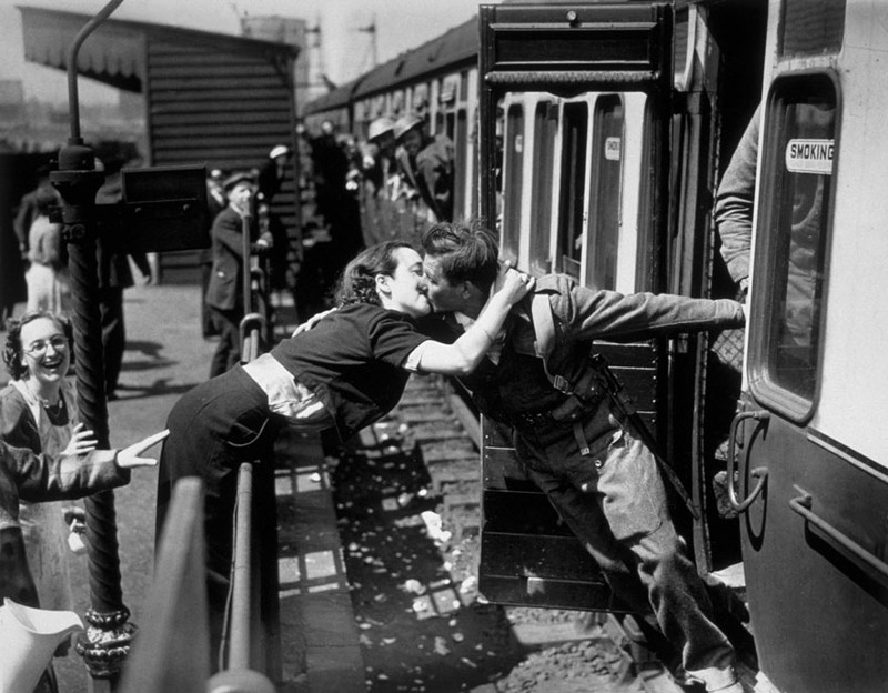 Một phụ nữ rướn người qua rào chắn để hôn người yêu vừa từ chiến trường Thế Chiến II trở về, 1940