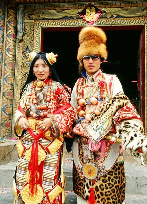 [Caption]Ở Tây Tạng, vào đêm trước ngày cưới, chú rể sẽ mang váy cưới và các phụ kiện khác cho cô dâu của mình. Trang phục thường bao gồm một chiếc khăn trùm, vòng bằng bạc để trang trí tóc và một bùa hộ mệnh nhỏ bằng kim loại nhỏ của nhà Phật.