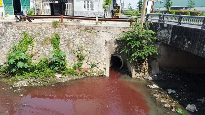 Nguồn nước đỏ chảy ra miệng cống dưới chân cầu bản Hy Vọng, đường Tân Sơn.