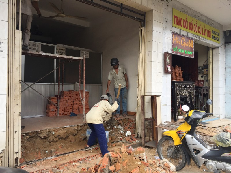 Nhà 63 Trường Chinh (quận Tân Bình, TP.HCM) đã bị đập bỏ bậc thềm hồi tuần trước. Hiện nhà này đã thuê thợ đến để đập sàn nhà, thi công bậc thềm mới phía trong nhà để không lấn chiếm vỉa hè. Ảnh: QUỲNH NHƯ