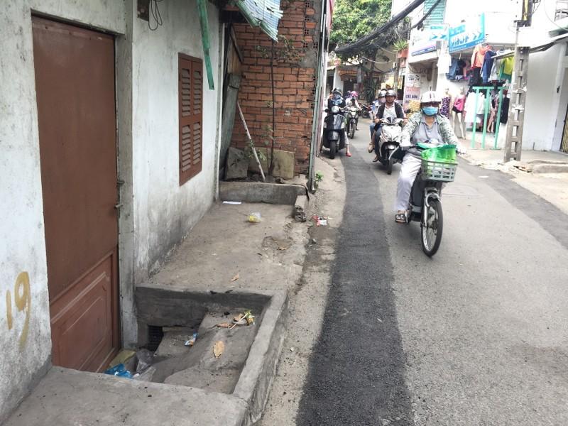 """Rất cần hạ tầng chỉn chu để người dân không phải trèo lên hay """"tuột xuống"""" nhà mình. Một ngôi nhà trên đường Bùi Đình Túy, quận Bình Thạnh có một nửa cửa thấp hơn mặt đường. Ảnh: Quỳnh Như"""