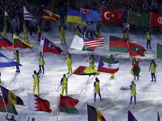 Các tình nguyện viên cầm cờ các quốc gia tham dự