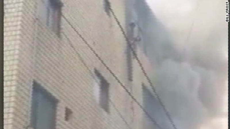 Mẹ thả 3 đứa con từ tầng lầu đang cháy lớn, sống sót kỳ diệu - ảnh 1