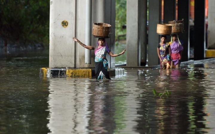 Người đi bộ đội giỏ trên đầu khi lội qua đường ngập lụt sau cơn mưa giông lớn ở Mumbai.