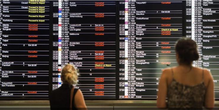 Hành khách theo dõi bảng hiển thị danh sách các chuyến bay bị hũy và bị hoãn lại ở Hong Kong. Ảnh: AFP