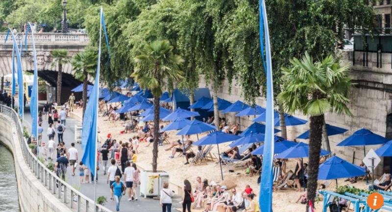 Du khách tắm nắng tại bãi tắm nhân tạo dọc bờ sông Seine ở Paris, Pháp. Ảnh: EPA
