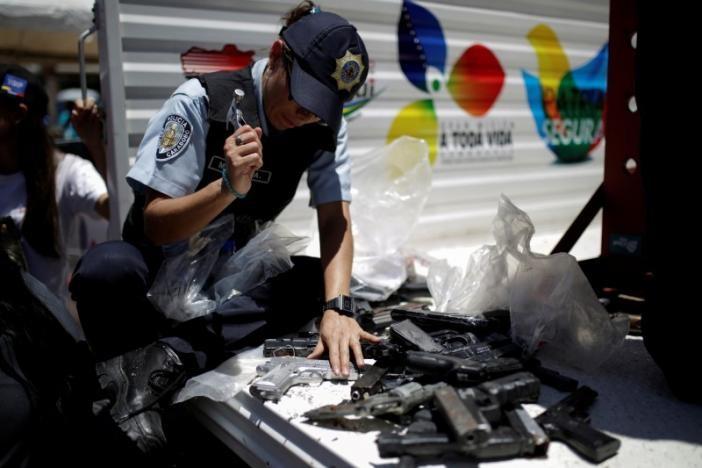 Cảnh sát đập vỡ các khẩu súng ngắn bị thu giữ. Ảnh: Reuters
