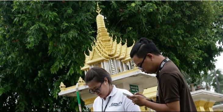Các phóng viên Thái Lan chơi Pokemon Go trước một tòa nhà . Ảnh: AP