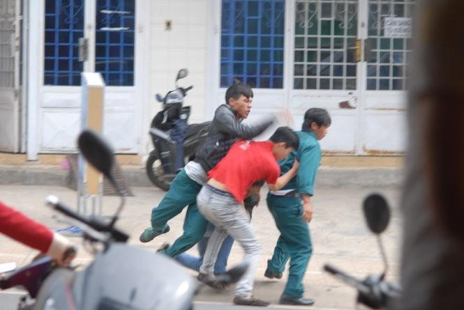 Lập tức người mặc trang phục dân quân tự vệ lao vào đánh đấm túi bụi người thanh niên mặc thường phục trước sự sửng sốt của nhiều người chứng kiến