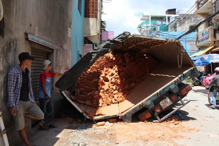 Xe tải sụp hố ga lật chổng vó giữa phố Sài Gòn - ảnh 1