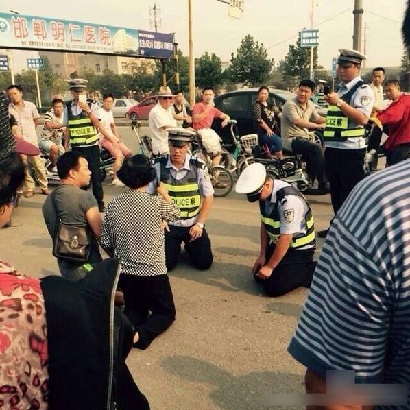 Cảnh sát giao thông quỳ xuống đất để giải thích cho dân - ảnh 1