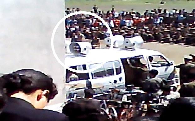 Hai người đàn ông (khoanh tròn) bị đem ra xét xử công khai trước đám đông dân chúng - Ảnh: cắt từ clip
