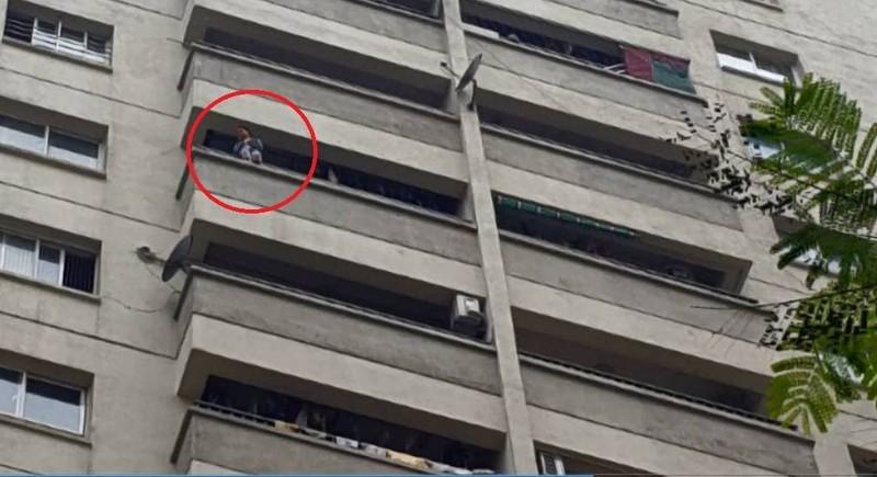Cháu bé ngồi vắt vẻo trên ban công tầng 12 (Ảnh cắt từ clip của anh Nguyễn Hà).